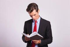 Молодая книга чтения бизнесмена Стоковые Фотографии RF