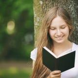 Молодая книга чтения девочка-подростка около дерева Стоковое Изображение
