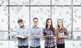 Молодая команда дела в офисе с падать бумаг Стоковые Фотографии RF