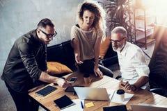 Молодая команда успешного бизнесмена делая большое обсуждение в современной coworking студии Бородатый человек разговаривая с Стоковые Фото