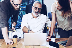 Молодая команда успешного бизнесмена делая большое обсуждение в современной coworking студии Бородатый человек разговаривая с Стоковая Фотография RF