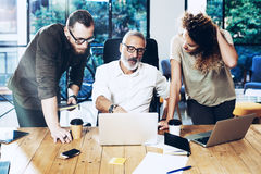 Молодая команда успешного бизнесмена делая большое обсуждение в современной coworking студии Бородатый человек разговаривая с Стоковое фото RF