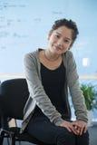 Молодая коммерсантка в вскользь одеждах сидя в офисе, портрете Стоковое Фото