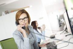 Молодая коммерсантка говоря на телефоне на столе в офисе Стоковое Изображение