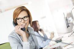 Молодая коммерсантка говоря на телефоне на столе в офисе Стоковые Изображения