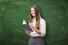 Молодая коммерсантка держа ее плановика дня открытых дверей и идя написать что-то Стоковое фото RF