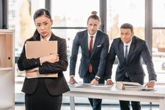 Молодая коммерсантка держа папку и бизнесмены стоя позади Стоковые Фотографии RF