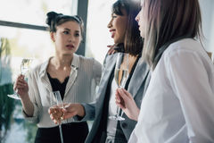 Молодая коммерсантка держа стекла шампанского и говоря в офисе Стоковое Фото