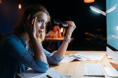 Молодая коммерсантка держа eyeglasses и смотря экран настольного компьютера Стоковые Фотографии RF