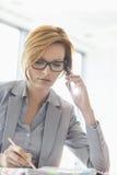 Молодая коммерсантка на звонке пока пишущ на столе в офисе Стоковое Изображение