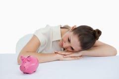 Молодая коммерсантка полагаясь на ее столе с piggy банком Стоковые Фотографии RF