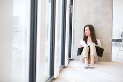 Молодая коммерсантка при файл смотря через окно офиса пока сидящ на поле Стоковые Фотографии RF