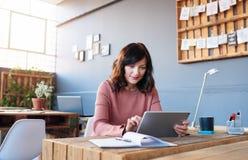 Молодая коммерсантка работая на ее столе с цифровой таблеткой Стоковое фото RF