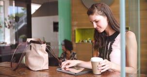Молодая коммерсантка работая на таблетке цифров в кофейне сток-видео
