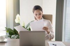 Молодая коммерсантка сидя на деятельности стола офиса, смотря thro Стоковые Изображения