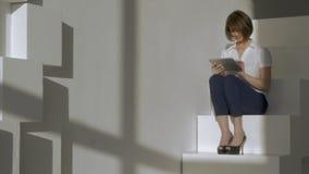 Молодая коммерсантка сидя на шагах, печатающ в ее таблетке и усмехаться акции видеоматериалы