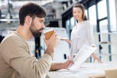 Молодая коммерсантка смотря кофе бизнесмена выпивая и смотря контракт Стоковые Фото