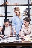 Молодая коммерсантка смотря коллег сидя на таблице и работая с бумагами Стоковое Изображение RF