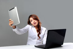 Молодая коммерсантка смотря таблетку пока говорящ на пэ-аш Стоковые Изображения RF