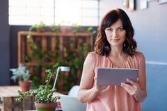 Молодая коммерсантка стоя в офисе используя цифровую таблетку Стоковые Фотографии RF