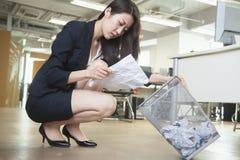Молодая коммерсантка читая кусок бумаги от мусорного бака в офисе Стоковая Фотография