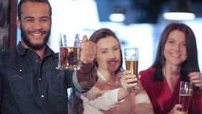 Молодая компания поднимает вверх стекло пива видеоматериал