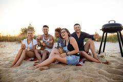 Молодая компания друзей радуясь, отдыхая на пляже во время восхода солнца Стоковые Фотографии RF