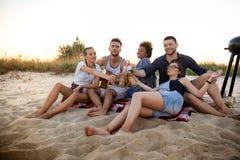 Молодая компания друзей радуясь, отдыхая на пляже во время восхода солнца Стоковое Фото