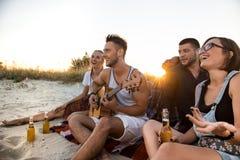 Молодая компания друзей радуясь, отдыхая на пляже во время восхода солнца Стоковые Изображения