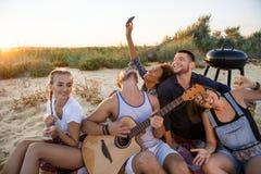 Молодая компания друзей радуясь, отдыхая на пляже во время восхода солнца Стоковая Фотография