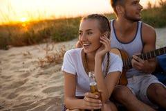 Молодая компания друзей радуясь, отдыхая на пляже во время восхода солнца Стоковое Изображение