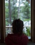 Молодая коричневая с волосами женщина смотря вне окно дома на лесе на дождливый день Стоковое Изображение RF