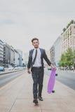 Молодая красивая азиатская модель идя с его скейтбордом Стоковое фото RF