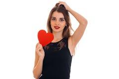Молодая красивая дама брюнет с красным сердцем в руках представляя и смотря камеру изолированную на белой предпосылке Стоковая Фотография