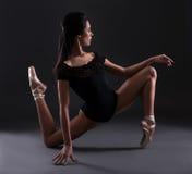Молодая красивая балерина женщины в костюме черного тела представляя над b Стоковые Изображения