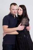 Молодая красивая беременная женщина и ее супруг над серым цветом Стоковые Фото