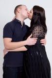 Молодая красивая беременная женщина и ее супруг целуя над серым цветом Стоковые Изображения RF