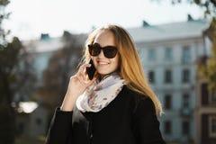 Молодая красивая белокурая девушка в солнечных очках говоря телефон Стоковые Фото
