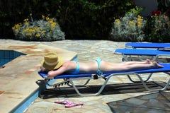 Молодая красивая белокурая девушка загорая на летний день на lounger бассейном Стоковые Фото