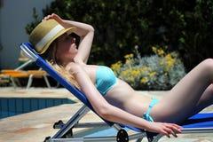 Молодая красивая белокурая девушка загорая на летний день на lounger бассейном Стоковые Изображения