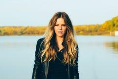 Молодая красивая белокурая женщина в парке осени с озером в зубах темной улыбки кожаной куртки совершенных во время захода солнца Стоковые Изображения RF