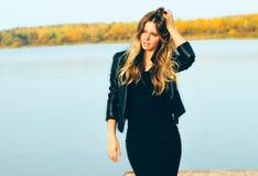 Молодая красивая белокурая женщина в парке осени с озером в зубах темной улыбки кожаной куртки совершенных во время захода солнца Стоковое фото RF
