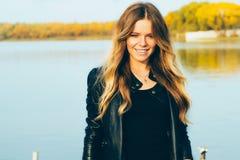 Молодая красивая белокурая женщина в парке осени с озером в зубах темной улыбки кожаной куртки совершенных во время захода солнца Стоковое Изображение RF