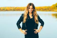 Молодая красивая белокурая женщина в парке осени с озером в зубах темной улыбки кожаной куртки совершенных во время захода солнца Стоковые Фотографии RF