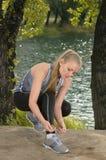 Молодая красивая белокурая женщина связывая шнурки ботинка спорта outdoors Стоковое Изображение