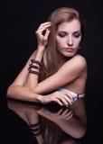 Молодая красивая белокурая женщина сидя на таблице зеркала на черном ба Стоковая Фотография