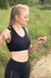 Молодая красивая белокурая музыка установки женщины на игроке перед утром, который побежали outdoors Стоковые Фотографии RF