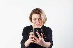 Молодая красивая бизнес-леди делает selfie на вашем телефоне против белой стены Стоковое Фото