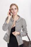 Молодая красивая блондинка бизнес-леди в черном платье говоря на телефоне на серой предпосылке Стоковые Изображения