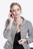 Молодая красивая блондинка бизнес-леди в черном платье говоря на телефоне на серой предпосылке Стоковое фото RF